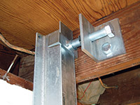 Securing the i-beam system to the top of the floor joist in a foundation wall repair in Saint Augustine.