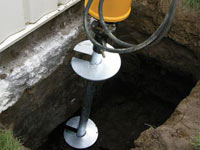 Installing a helical pier system in the earth around a foundation in Manhattan