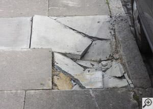 photo of a sinking concrete sidewalk with cracks in Saint Albans