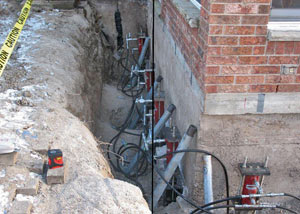 Foundation push piers installed around a house with a foundation settlement issues in Middle Village
