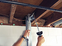 Straightening a foundation wall with the PowerBrace™ i-beam system in a Ridgewood home.