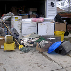 Soaked, wet personal items sitting in a driveway, including a washer and dryer in Astoria.